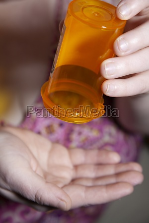 woman emptying medication bottle