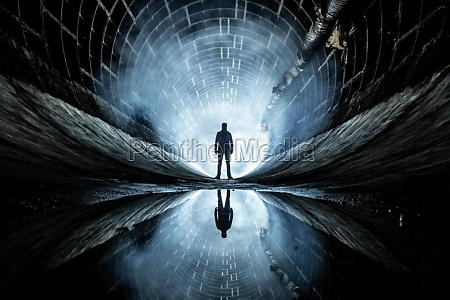 man stands in a tunnel against