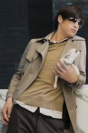 young man carrying a puppy