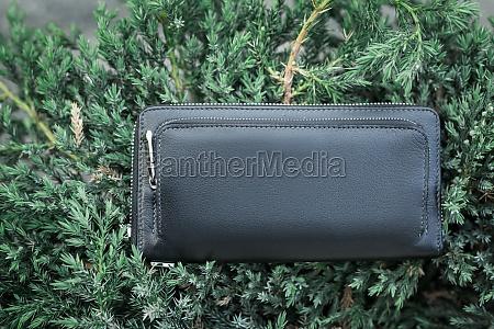black wallet purse on pavement white