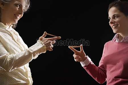 two businesswomen playing with rubber band