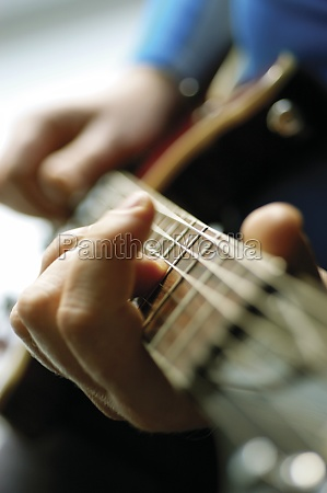 close up of man playing acoustic