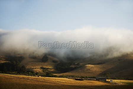 clouds rolling over a hill range