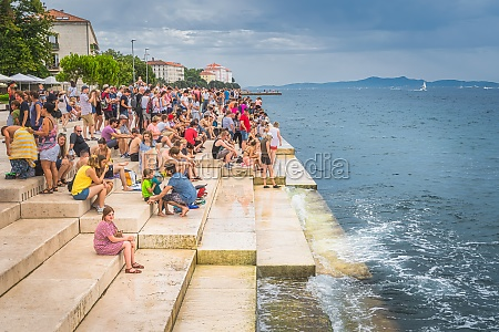 crowd of tourists listen to sea