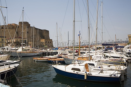 sailboats docked at a harbor with