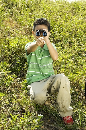 boy looking through a pair of