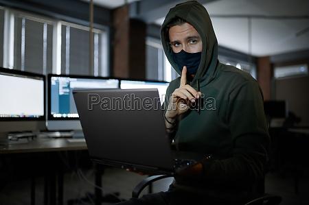 male hacker in hood works on