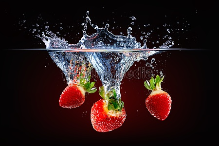fresh strawberries falling into splashing water