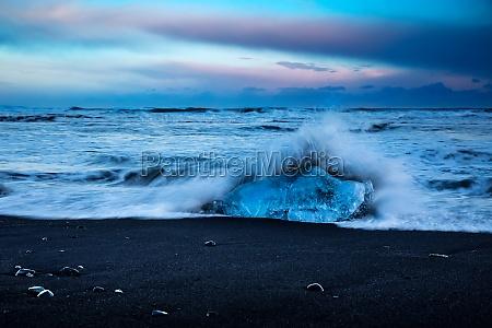 volcanic sand beach with icebergs