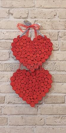 red hearts hang on brick wall