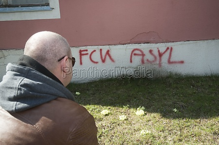 man looks at a graffiti that