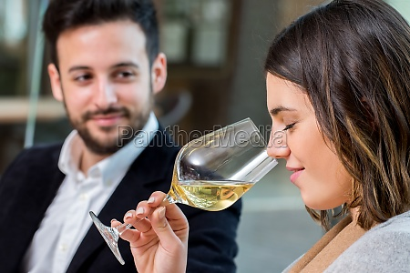 woman smelling white wine at tasting