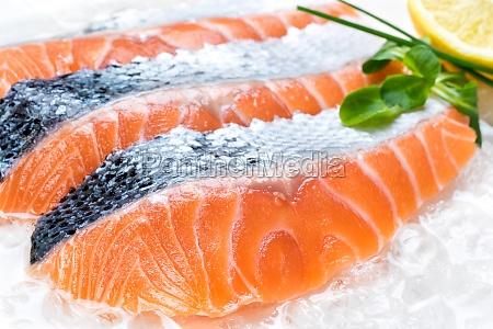 fresh sliced salmon portions on ice