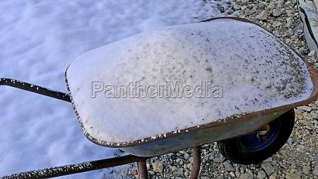 snow on a wheelbarrow in wintertime