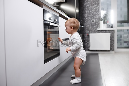 infant baby boy near oven in