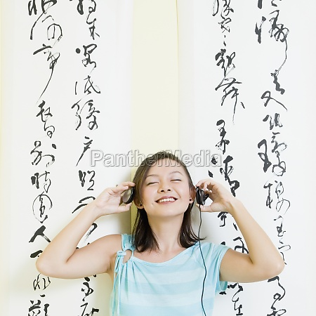 young woman wearing headphones and listening