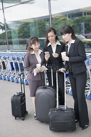 three businesswomen looking at a personal