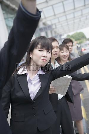 business executives hailing a taxi at