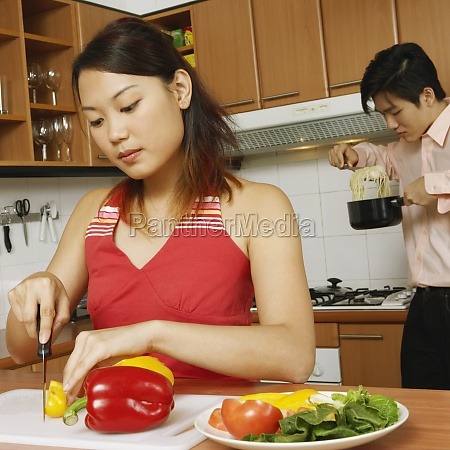 young woman cutting vegetables in the