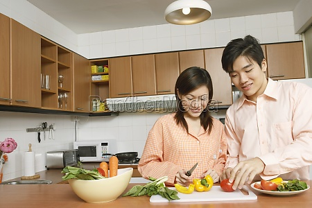 young couple cutting vegetables at a