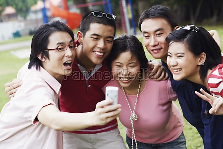 five people looking at a mobile