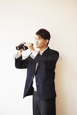 businessman holding a pair of binoculars