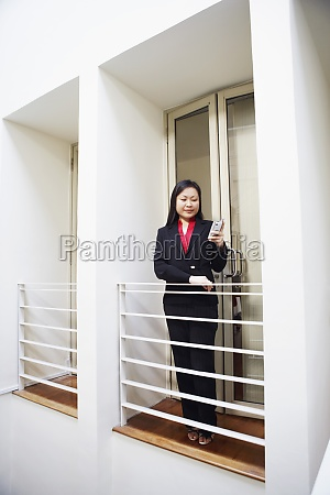 businesswoman standing along the railing and