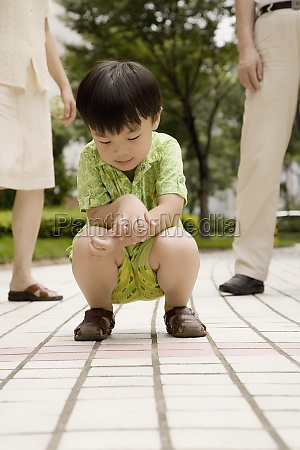 boy crouching on a footpath with