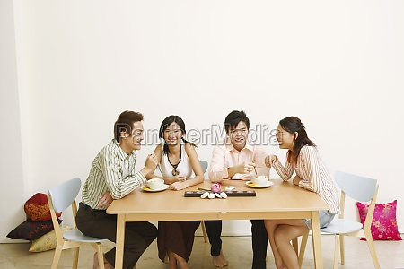 two young couples eating noodles and