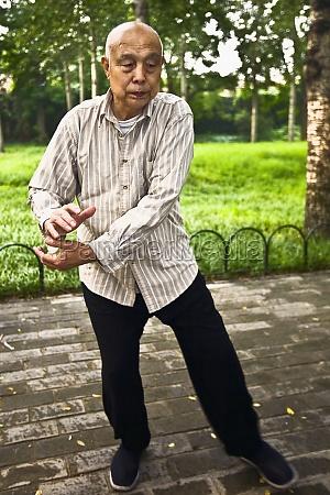 senior man practicing kung fu temple