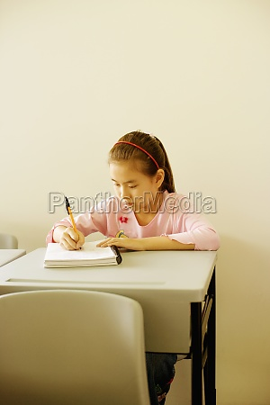 girl writing on a spiral notebook