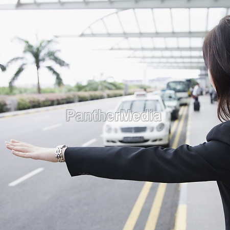 rear view of a businesswoman hailing