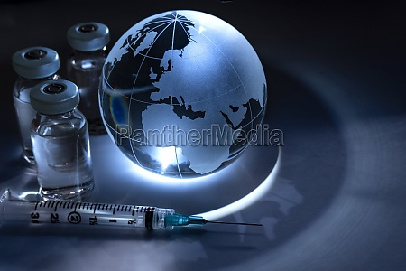 glass globe with vials and syringe