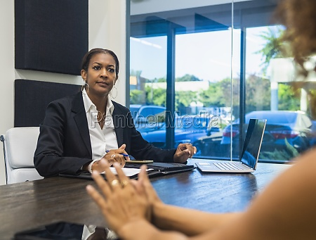 two businesswomen talking at conference table