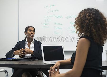 two businesswomen working in office