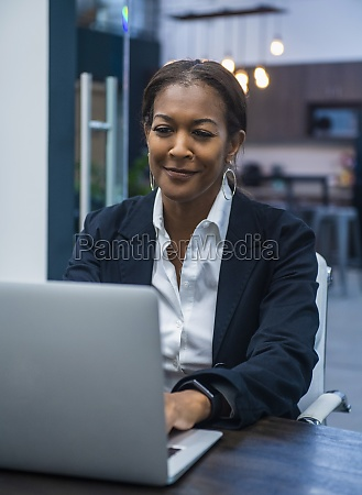 smiling businesswoman working on laptop at