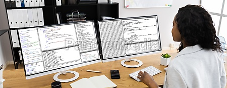 african coder using multiple computer screens