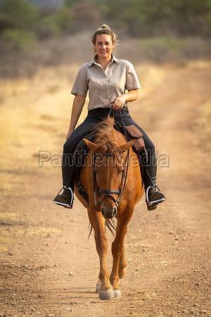 smiling blonde rides horse along dirt