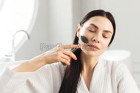 beautiful european woman uses jade roller