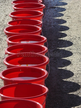 row of red buckets with shadow