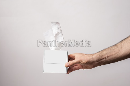 male hand holding a cubical tissue