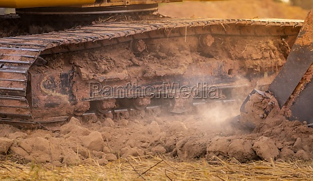backhoe working by digging soil at