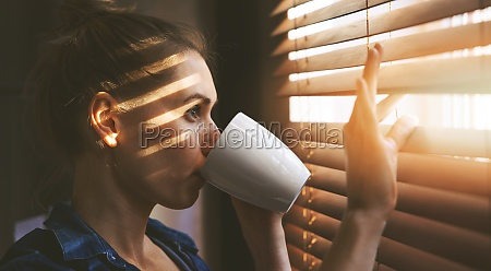 woman looking through window blinds into