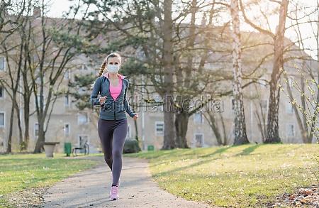 woman jogging down a path boosting