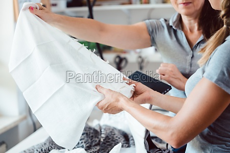 designers inspecting sample fabric in atelier