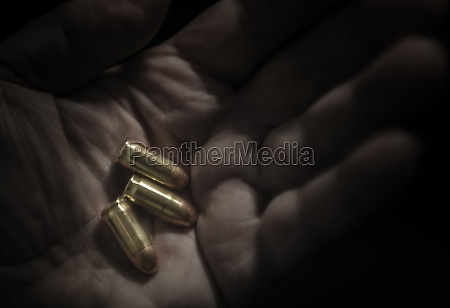 close up of hand holding bullets