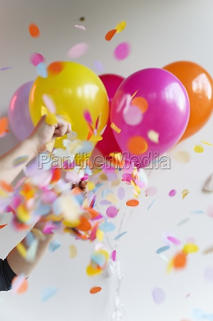 hand holding bunch of colorful balloons