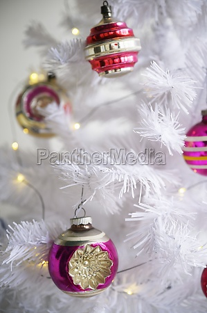 pink ornaments on white christmas tree