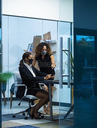 business women wearing masks in office