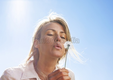 blond woman blowing dandelion